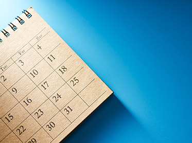 Image of a blank calendar page on a blue surface