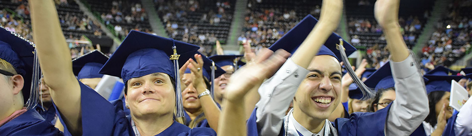 Students celebrate at graduation in their caps and gowns