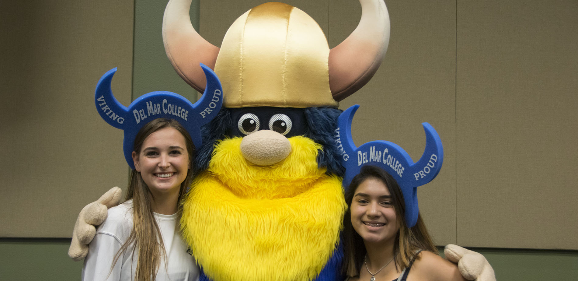 Valdar the Viking mascot poses with prospective students at orientation