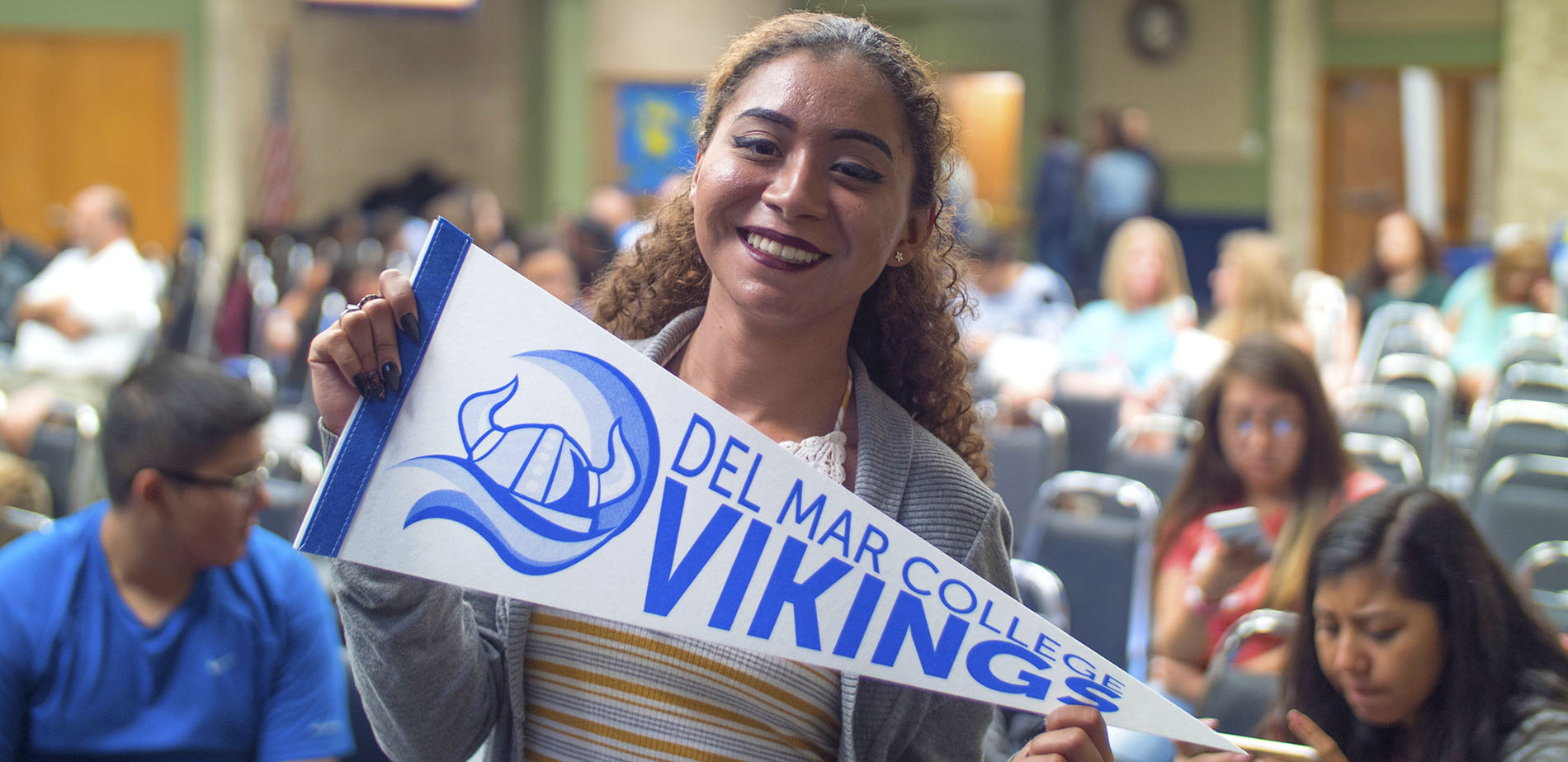 A student holding up a Del Mar College pennant