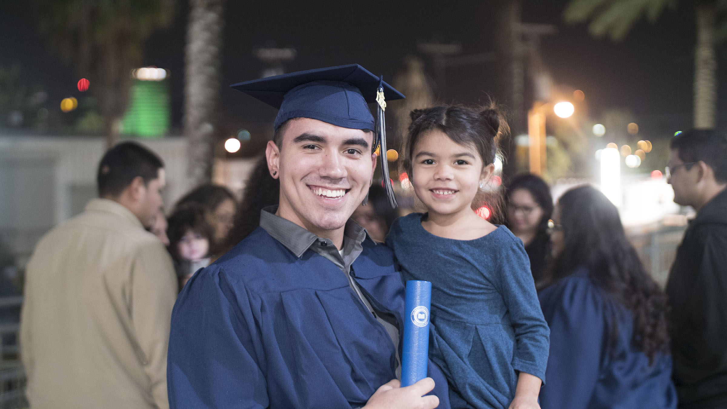 A smiling student poses in cap and gown while holding his degree and a young child